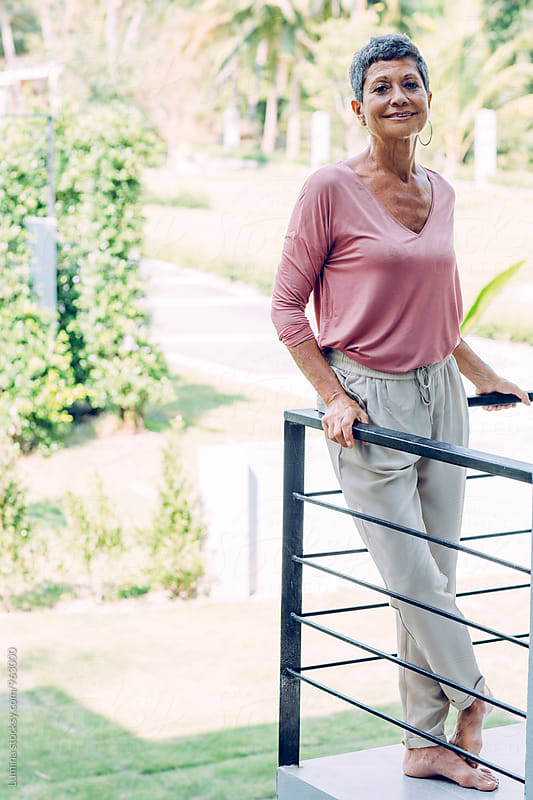 Senior Woman Standing on the Balcony at Home by Lumina for Stocksy United