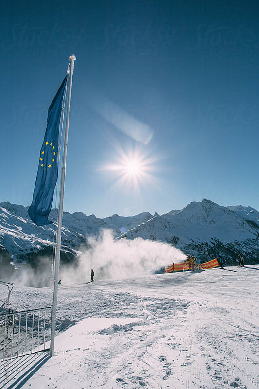 EU flag and snow cannon producing artificial snow in the European Alps  in winter by Soren Egeberg for Stocksy United