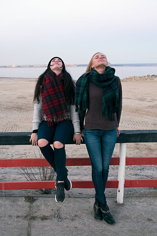 Two girls with eyes closed standing near wooden fence on beach by Danil Nevsky for Stocksy United