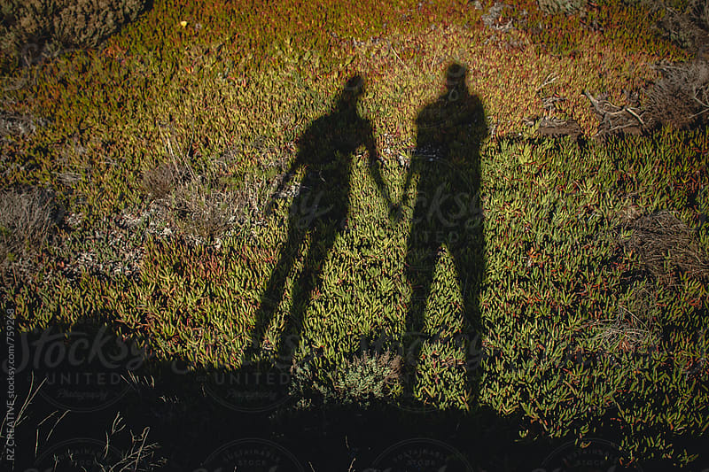 Shadow of couple holding hands. by Robert Zaleski for Stocksy United