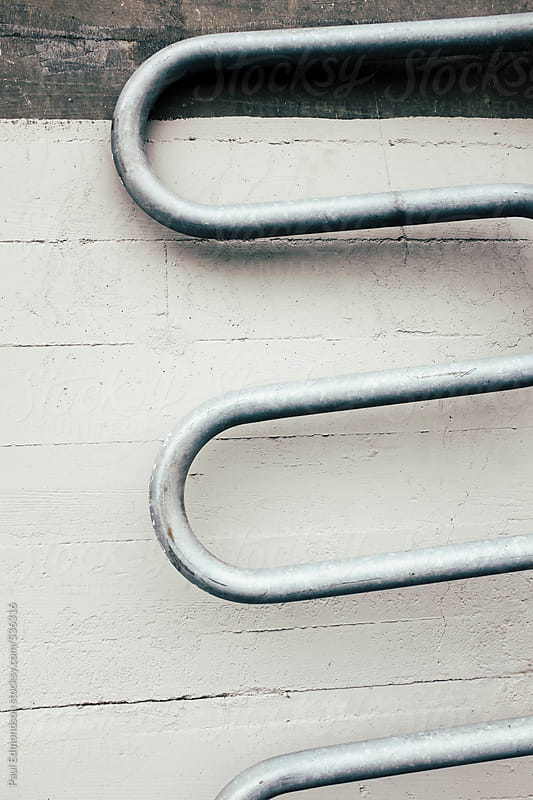 Curved metal bike rack leaning against concrete wall by Paul Edmondson for Stocksy United