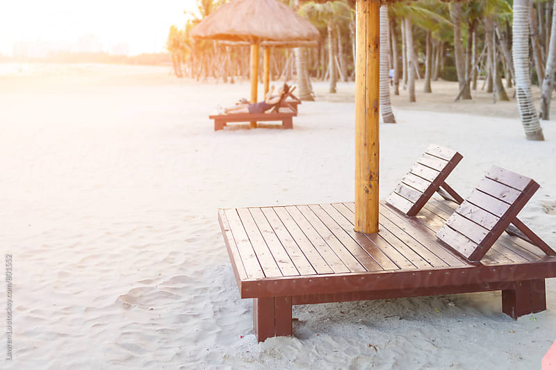 Wooden recliner chairs on a tropical beach under sunshine by Lawren Lu for Stocksy United