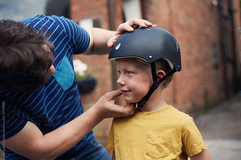 Father putting on sons safety helmet by sally anscombe for Stocksy United