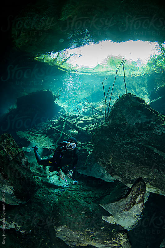 A scuba diver swimming in Mexico's  Cenote Kukulcan by Song Heming for Stocksy United
