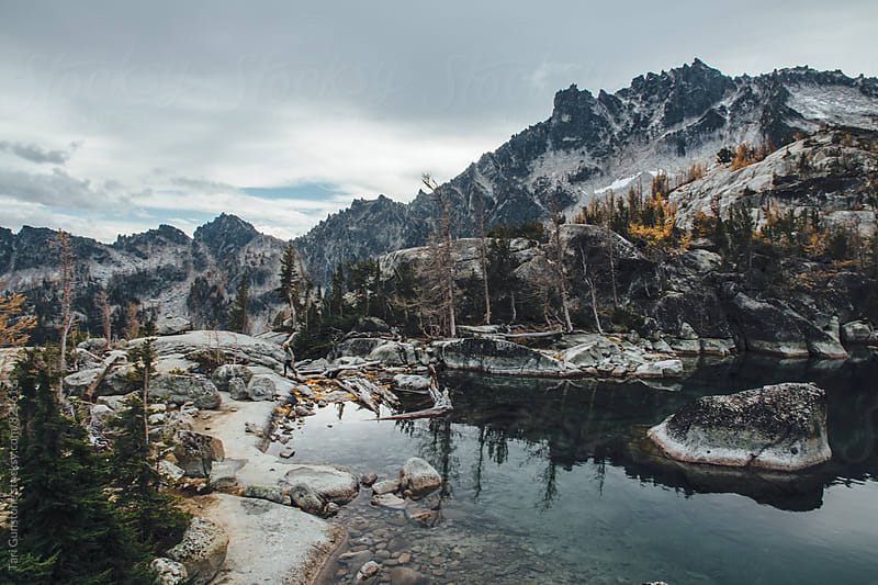 Hiker climbs along lake and mountain scenery by Tari Gunstone for Stocksy United