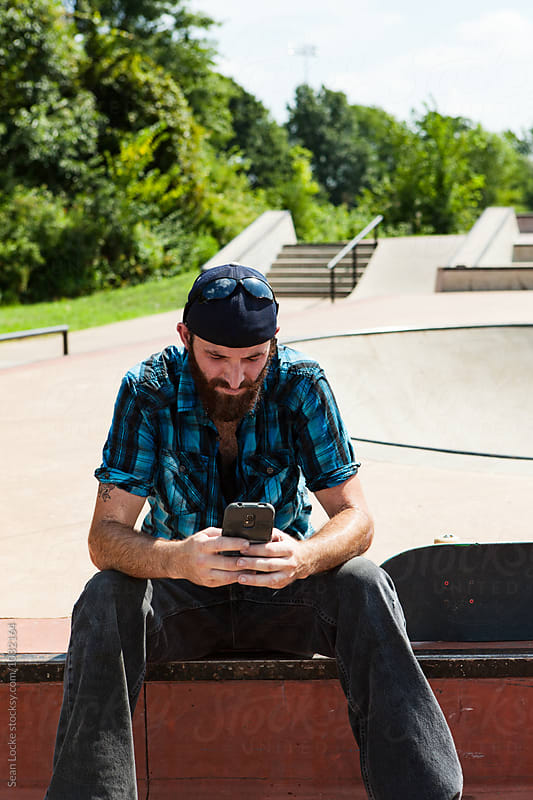 Skateboarder Resting And Checking Text Messages by Sean Locke for Stocksy United