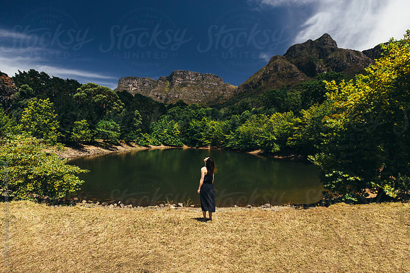 Woman standing and relaxing in nature by edge of lake surrounded by Mountains by Jonathan Caramanus for Stocksy United