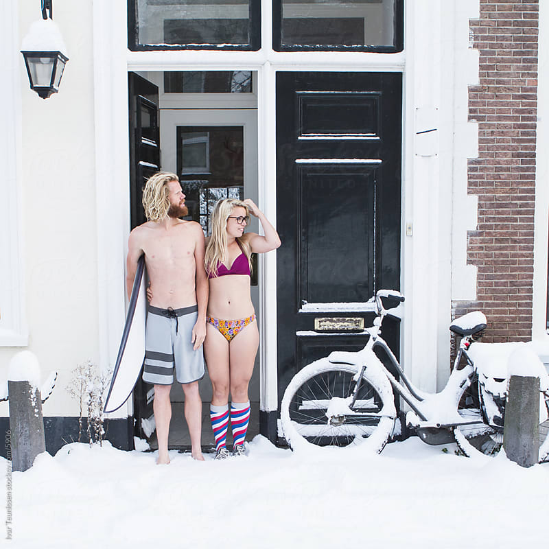 Young surfers standing in the snow, confused. by Ivar Teunissen for Stocksy United