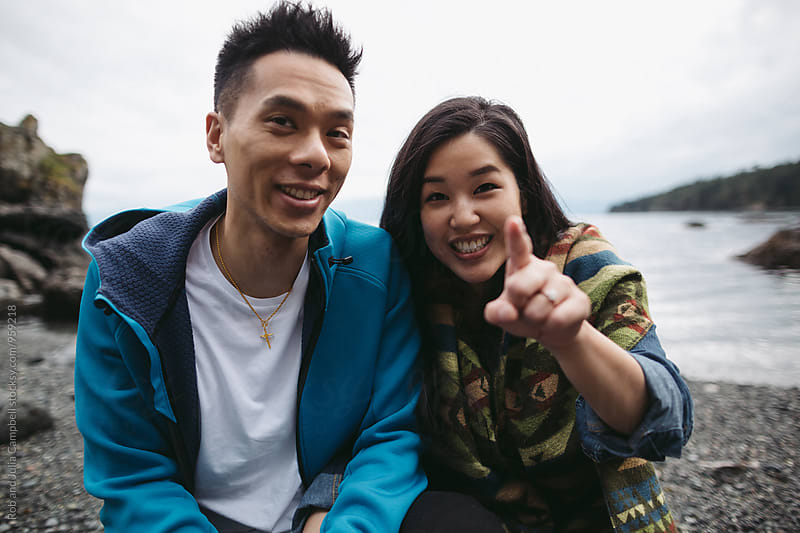 Young happy asian couple spending quality time together outside in nature by Rob and Julia Campbell for Stocksy United