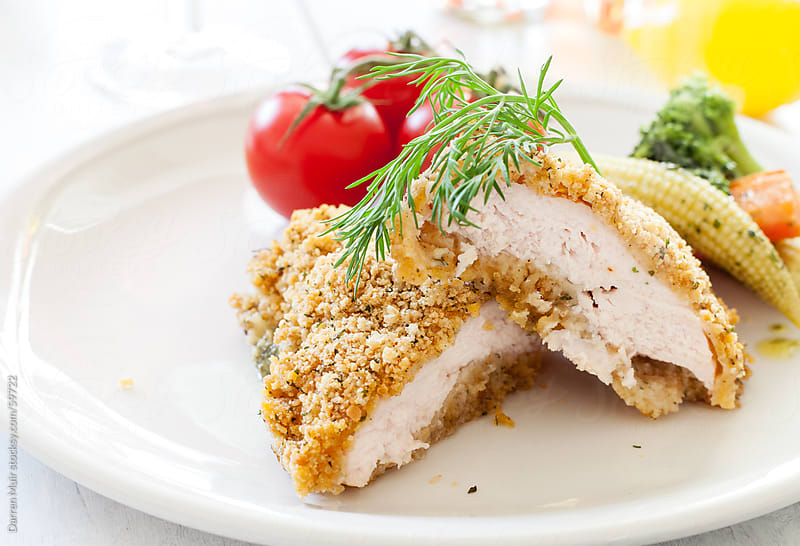 Herb crusted chicken breast. by Darren Muir for Stocksy United