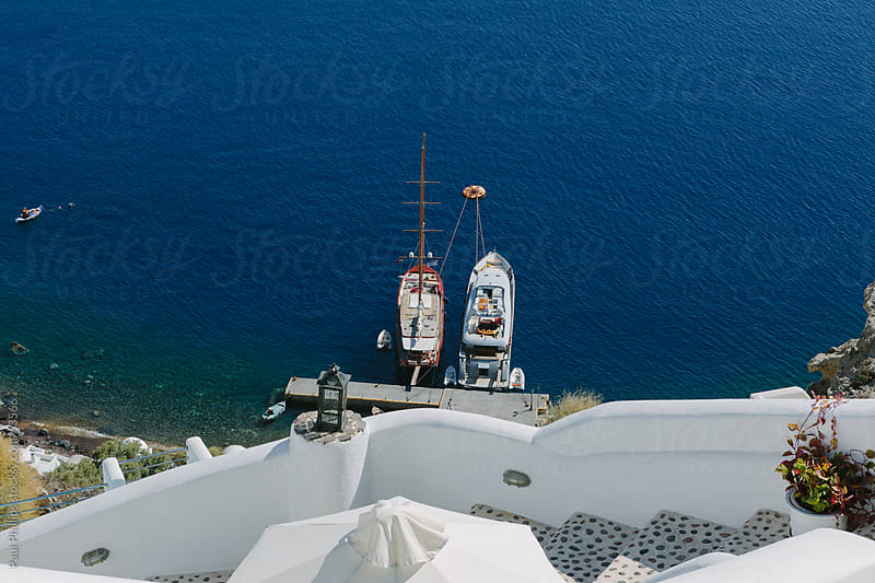 Two boats moored at the bottom of steps in Santorini by Paul Phillips for Stocksy United