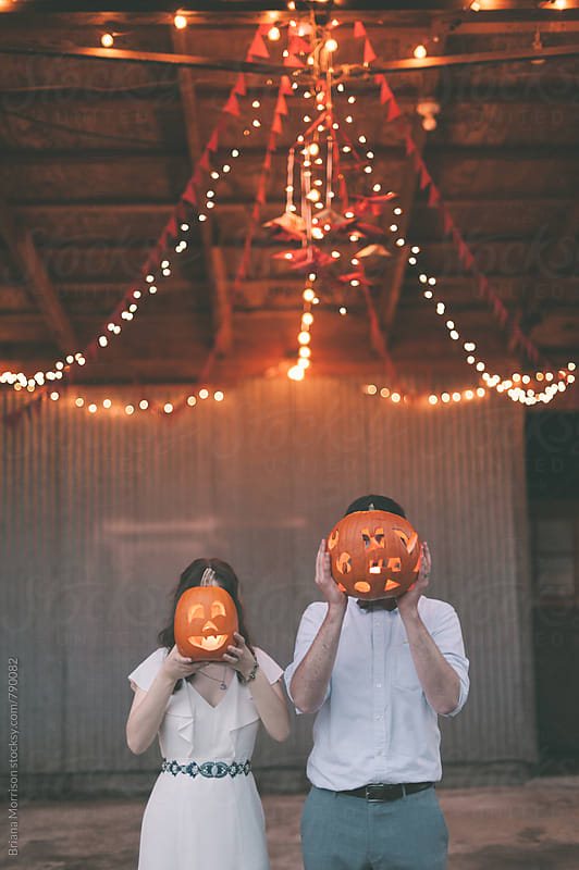 Wedding Couple with Jack-O-Lantern Decorations by Briana Morrison for Stocksy United