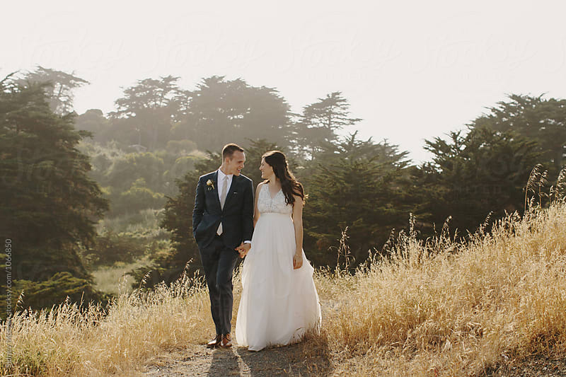 Bride and Groom Walking through Field by Sidney Morgan for Stocksy United