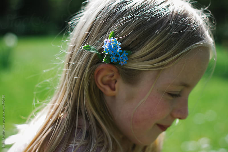 A little girl with forget-me-nots in her hair by Helen Rushbrook for Stocksy United