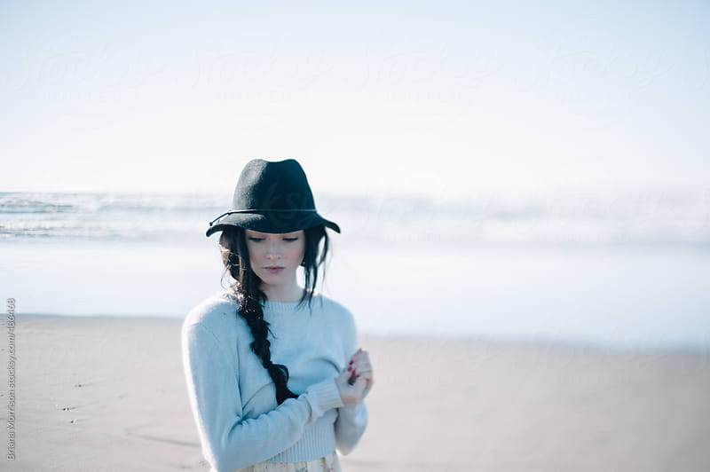 Thoughtful Young Woman Wearing A Black Hat on the Beach by Briana Morrison for Stocksy United