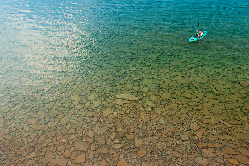 Woman in Kayak Paddling on Crystal Clear Freshwater Lake at Summer Family Cottage by JP Danko for Stocksy United