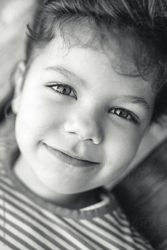 Black and white portrait of a cute smiling young girl by Lea Csontos for Stocksy United