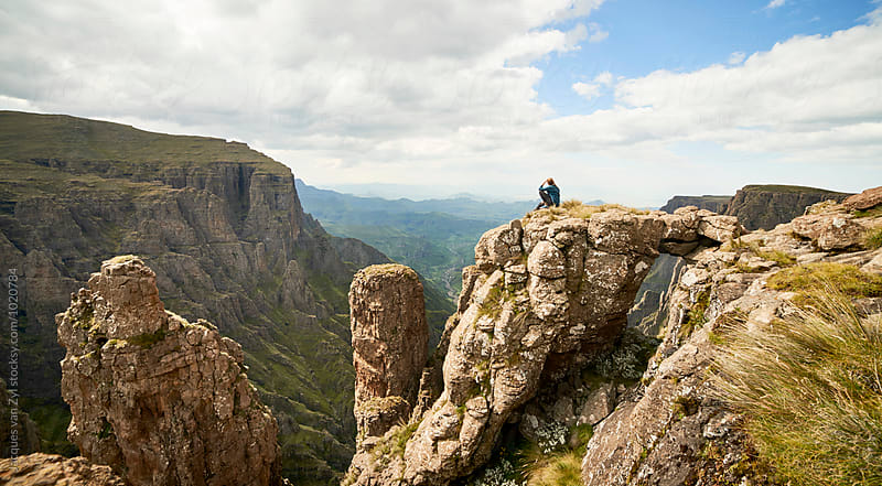 A Female hiker sitting on a rock spire with a with a natural bridge above an epic mountainous valley. by Jacques van Zyl for Stocksy United