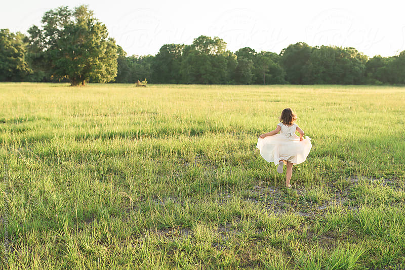 A Young Girl Runs Through An Open Field At Sunset  by Alison Winterroth for Stocksy United
