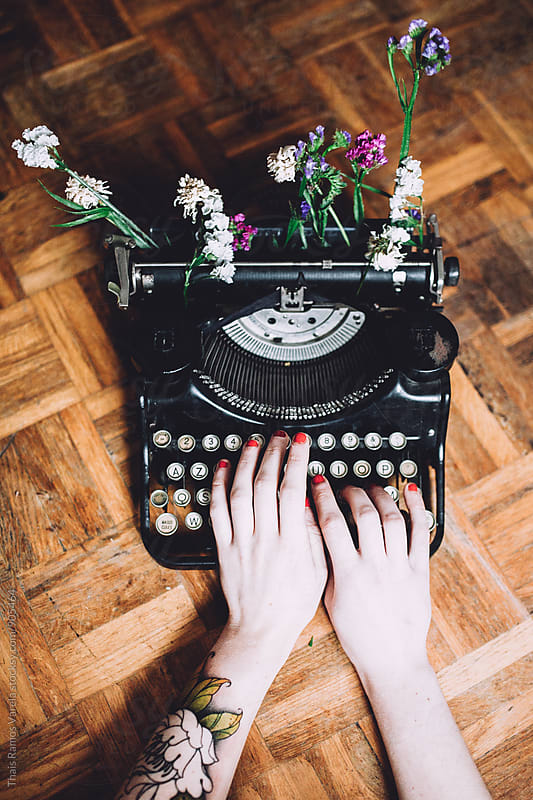 Woman typing with a vintage typewriter with flowers by Thais Ramos Varela for Stocksy United
