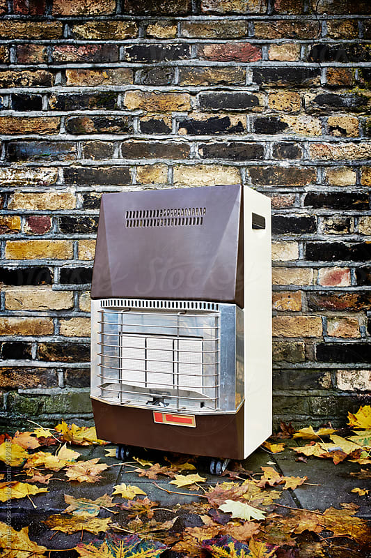 Gas heater left by a brick wall by James Ross for Stocksy United