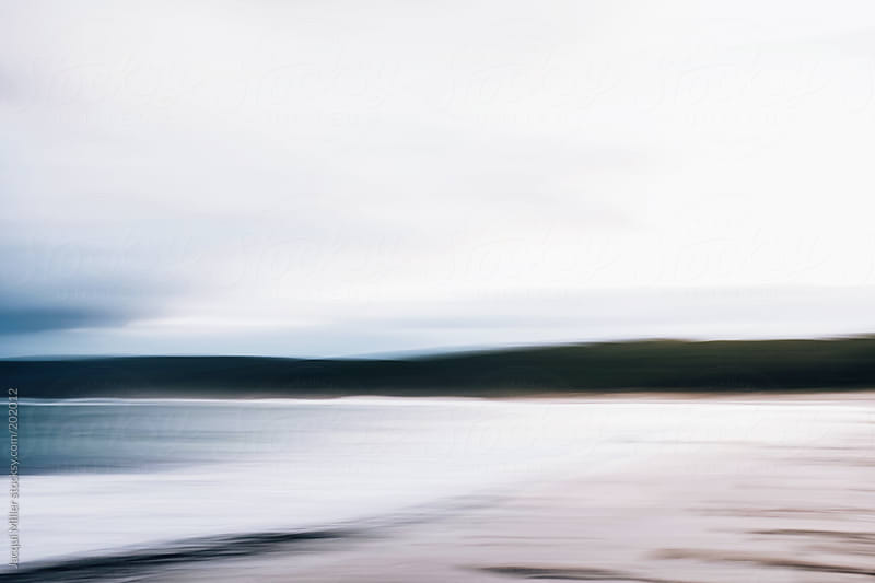 Early morning beach beneath a cloudy sky by Jacqui Miller for Stocksy United