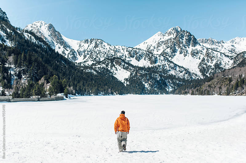 Back view of a mountaineer walking to the snowy lake by Jordi Rulló for Stocksy United
