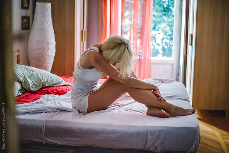 Worried woman sitting on the bed by GIC for Stocksy United