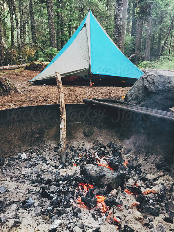 Campfire with Burning Coals with a Tent in the Background by michelle edmonds for Stocksy United