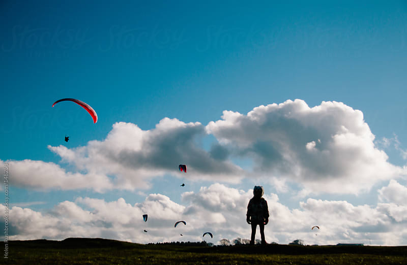 The silhouette of a little girl watching paragliders by Helen Rushbrook for Stocksy United