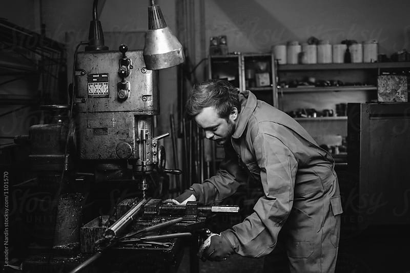 concentrated young metal worker operating a drilling machine - black and white by Leander Nardin for Stocksy United