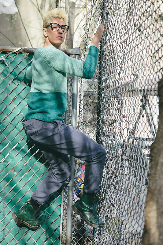 Stylish Young Man with Bleached Blond Hair in Spring and Summer Fashion Climbing a Fence by Joselito Briones for Stocksy United