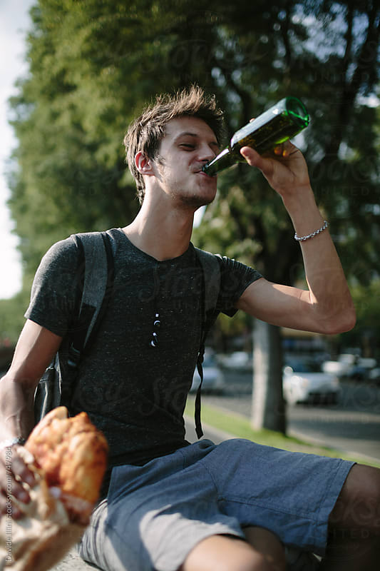 Young man eating pizza and drinking a beer outdoors by Davide Illini for Stocksy United