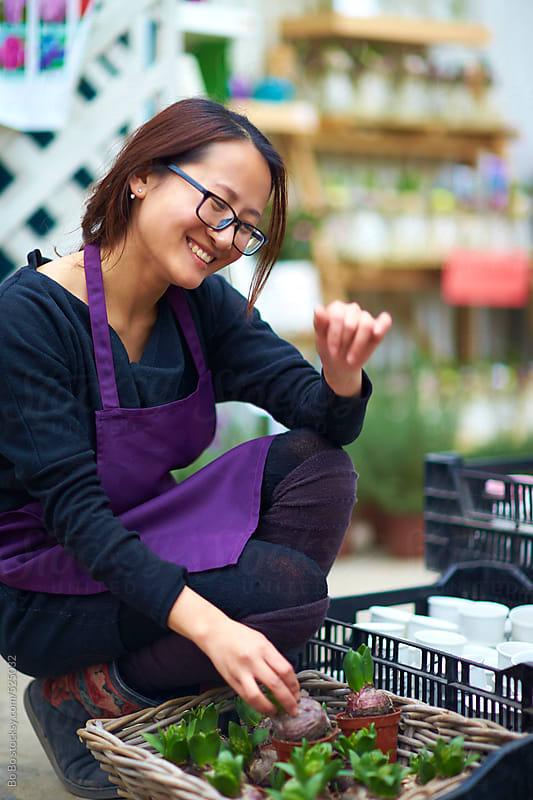 female florist in her shop  by Bo Bo for Stocksy United