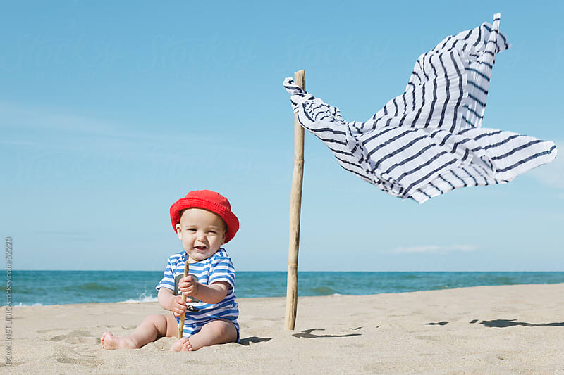 Castaway baby smiling sitting on the sand of the beach. by BONNINSTUDIO for Stocksy United