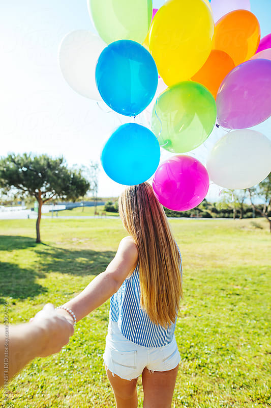 Back view of a girl walking with her boyfriend holding colorful balloons in a park. by BONNINSTUDIO for Stocksy United