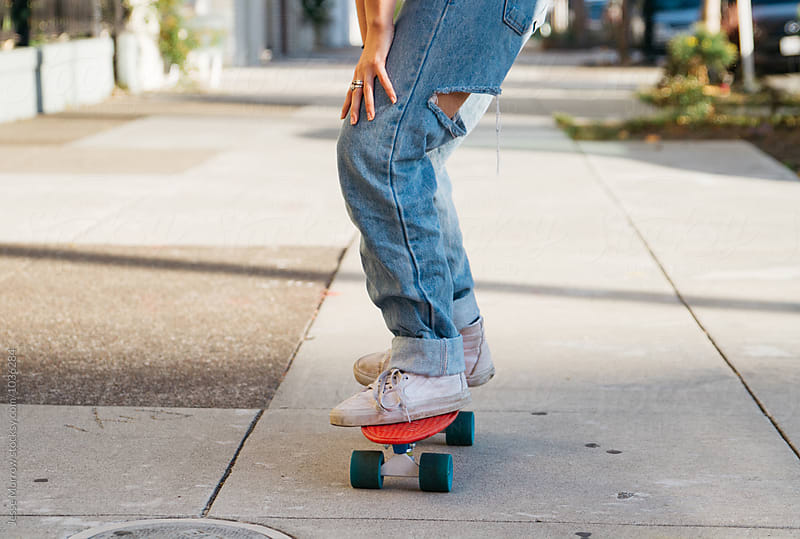 young woman wearing ripped jeans rides skate board in city  by Jesse Morrow for Stocksy United