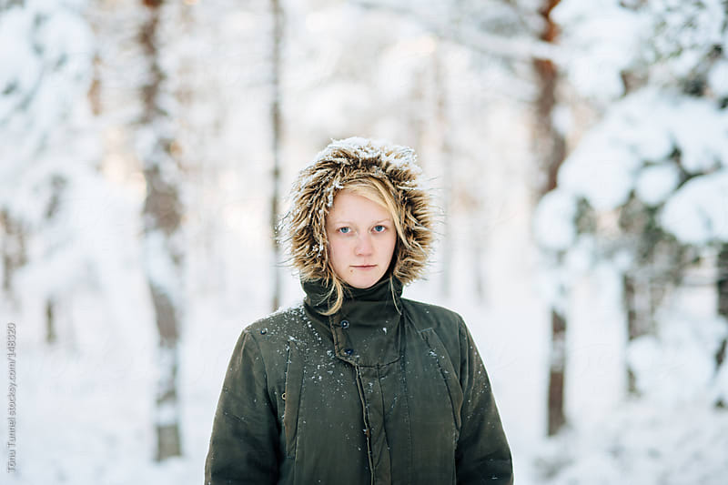 Scandinavian girl standing in a snowy forest by Tõnu Tunnel for Stocksy United