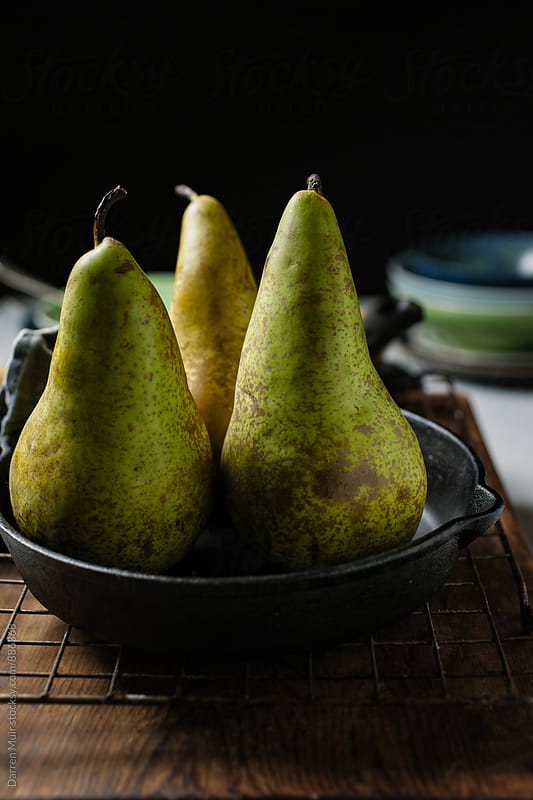Conference pears: Three pears in a cast iron pan,ready to be prepared for a recipe. by Darren Muir for Stocksy United