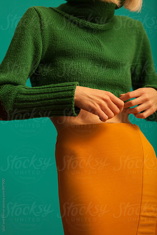 young woman with yellow skirt and green sweater standing by Ulaş and Merve for Stocksy United