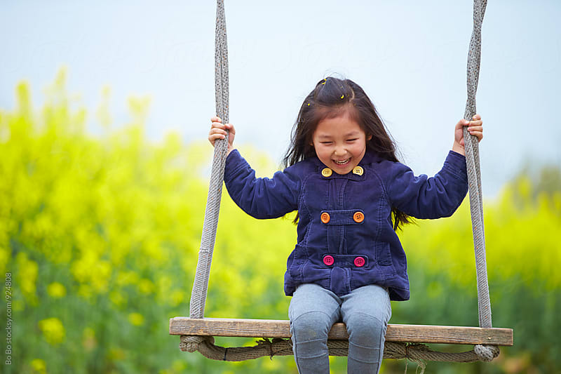 happy little girl on swing by Bo Bo for Stocksy United