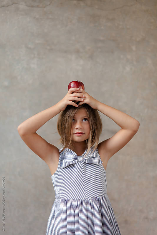 School girl wearing striped dress with bow holding an apple on her head by Amanda Worrall for Stocksy United