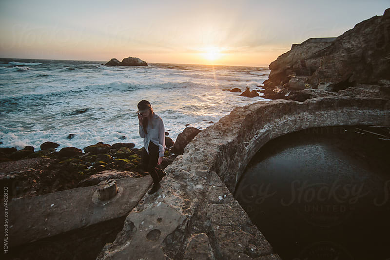 young girl walks along rock formation on California coast by HOWL for Stocksy United
