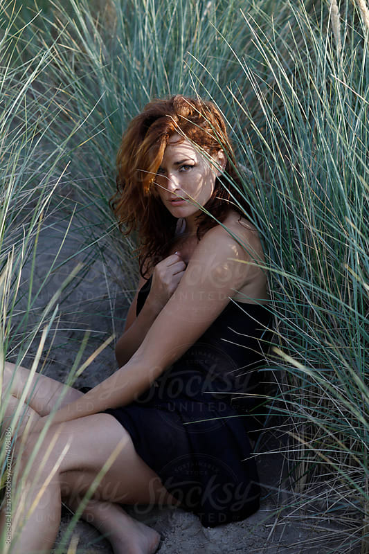 red haired girl sitting in dune by Rene de Haan for Stocksy United