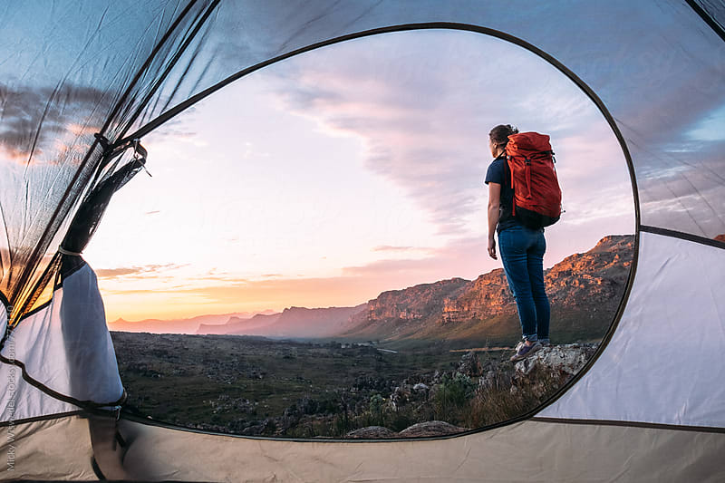 Female hiker with a backpack standing outside her tent watching a sunset by Micky Wiswedel for Stocksy United