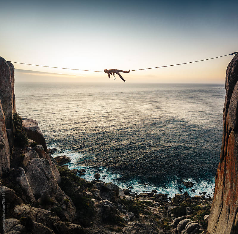 man lying on a tightrope highline between two cliffs overlooking the sea at sunset by Micky Wiswedel for Stocksy United