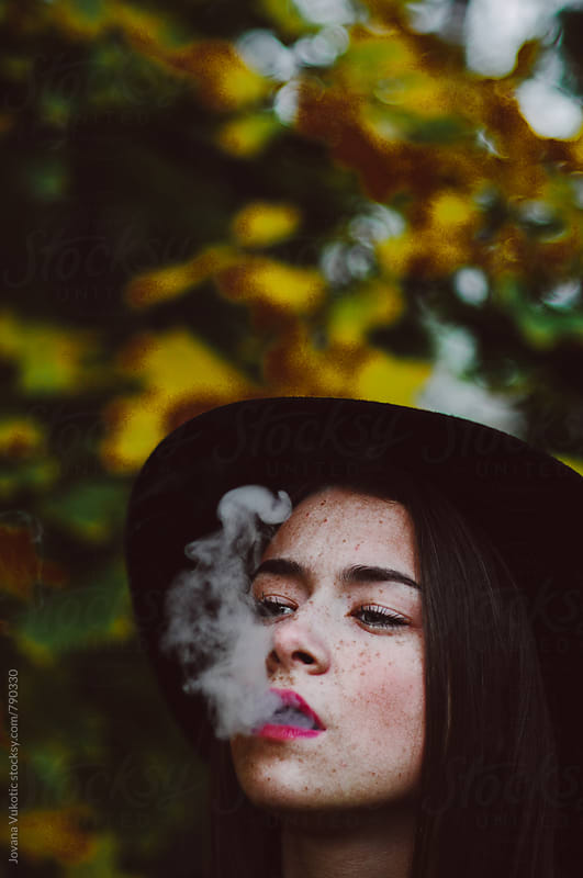 Woman smokes by Jovana Vukotic for Stocksy United