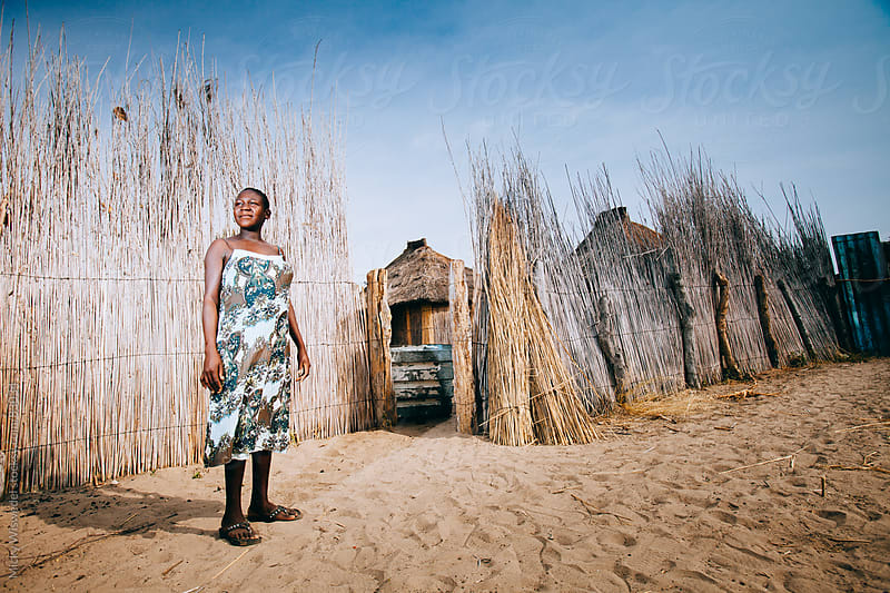 Proud young African Hambukushu woman outside her kraal by Micky Wiswedel for Stocksy United