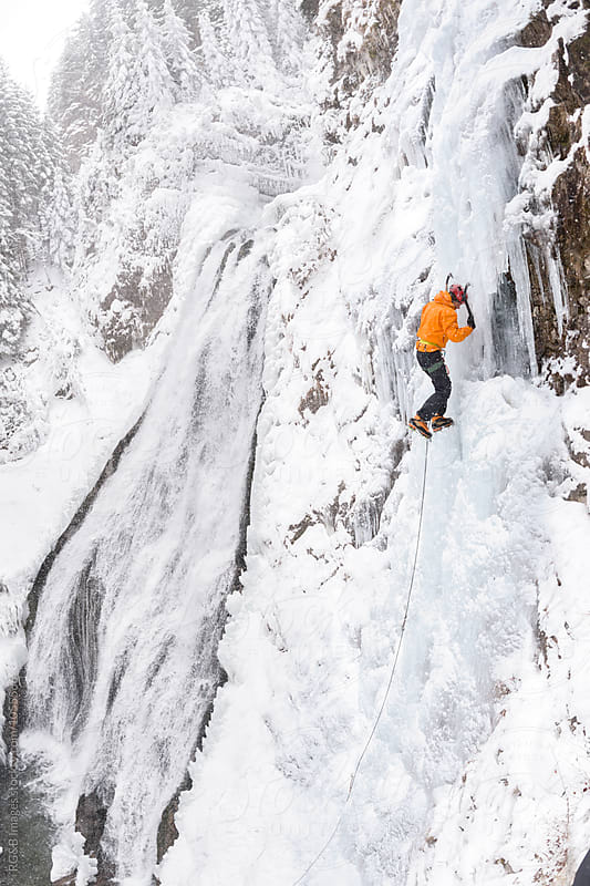 Ice climber ascending a frozen waterfall by RG&B Images for Stocksy United