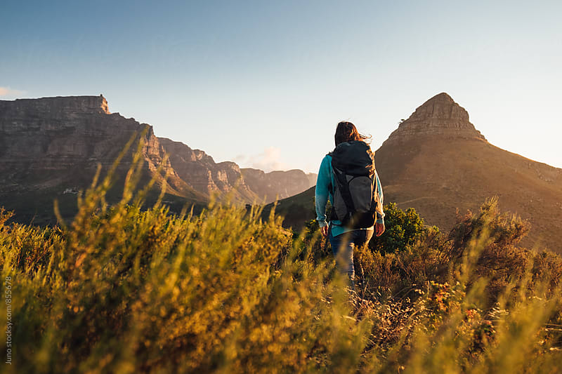 Woman with back hiking in the mountains at sunset by Micky Wiswedel for Stocksy United